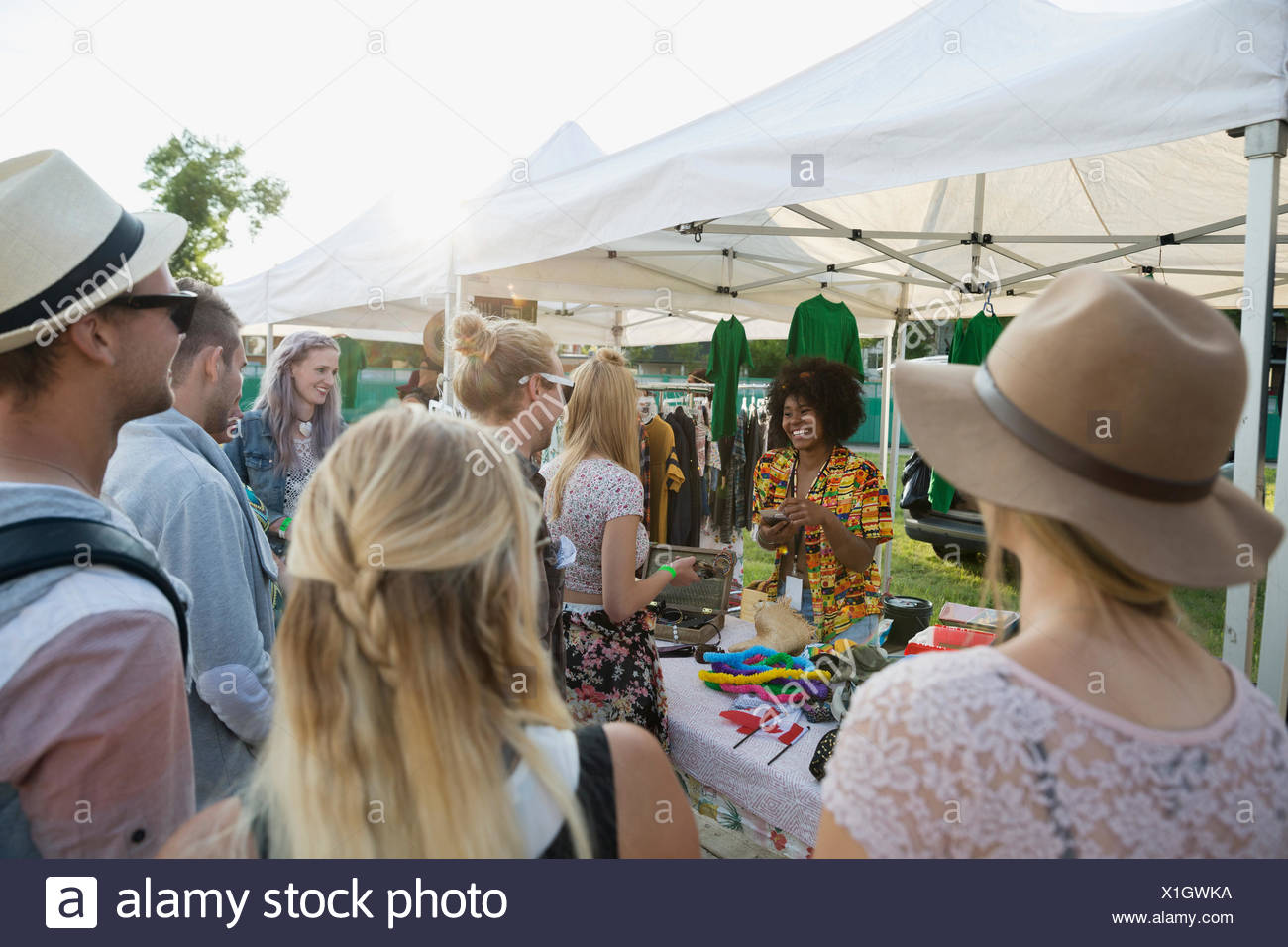 Young people at vendor booth at summer music festival - Stock Image