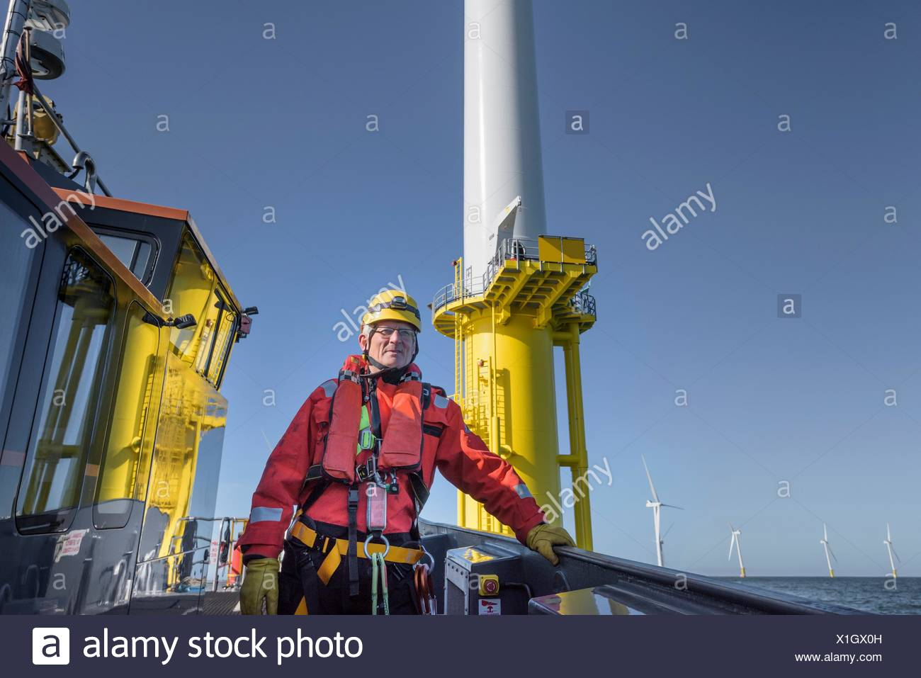 Portrait of engineer on boat on offshore wind farm - Stock Image