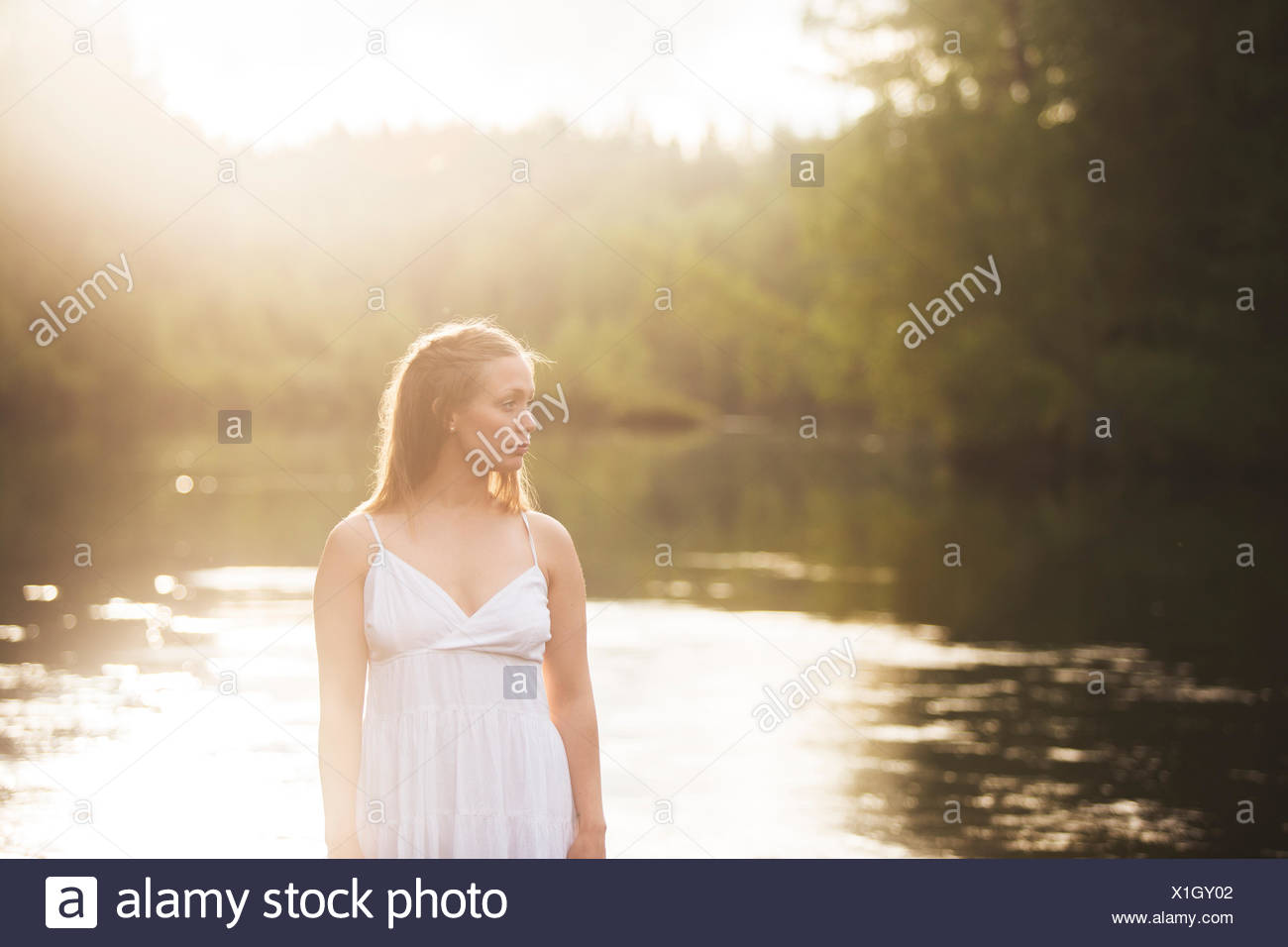Woman wearing white dress by river - Stock Image