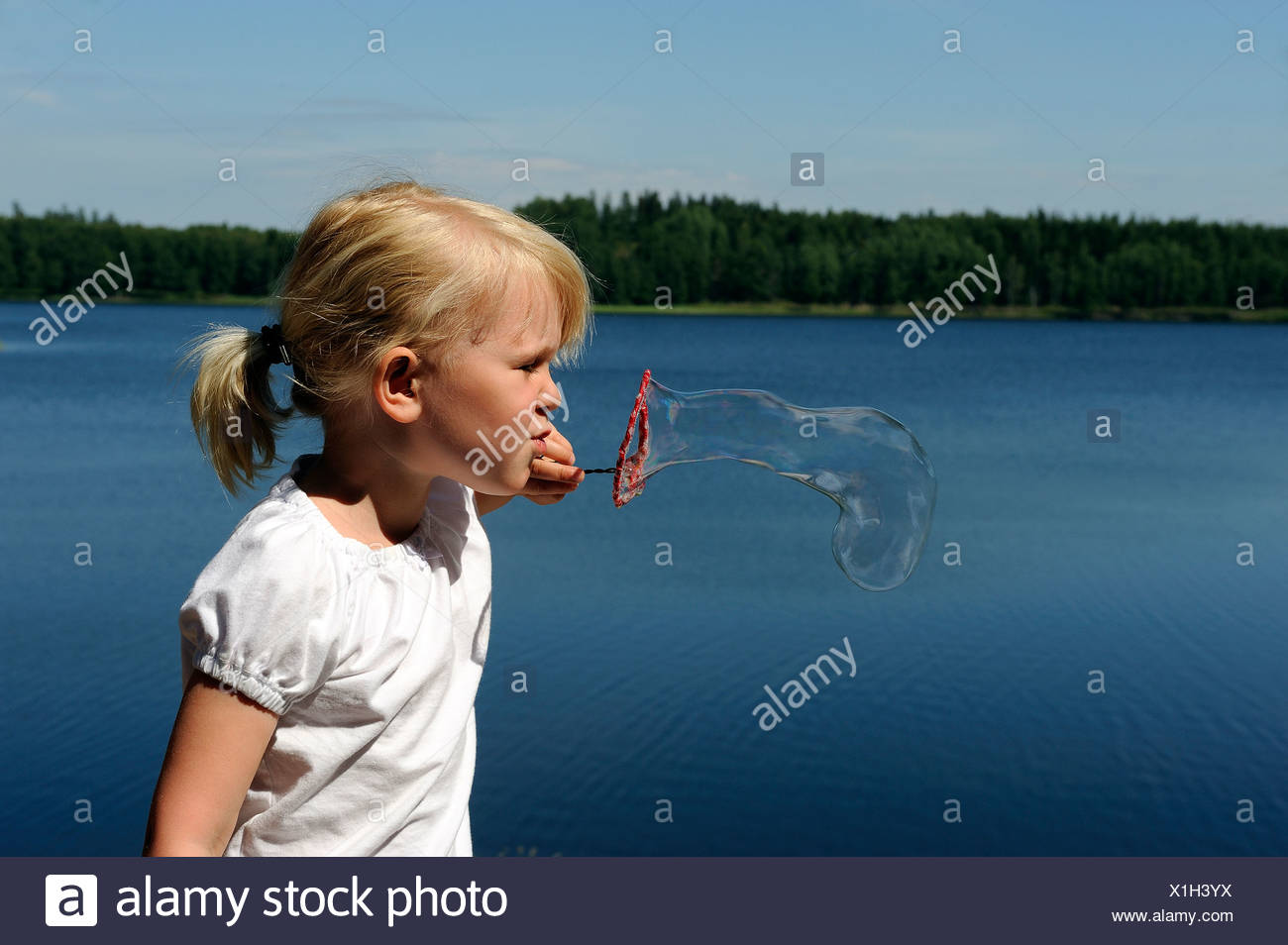 Side view of a girl blowing soap bubbles against peaceful lake - Stock Image