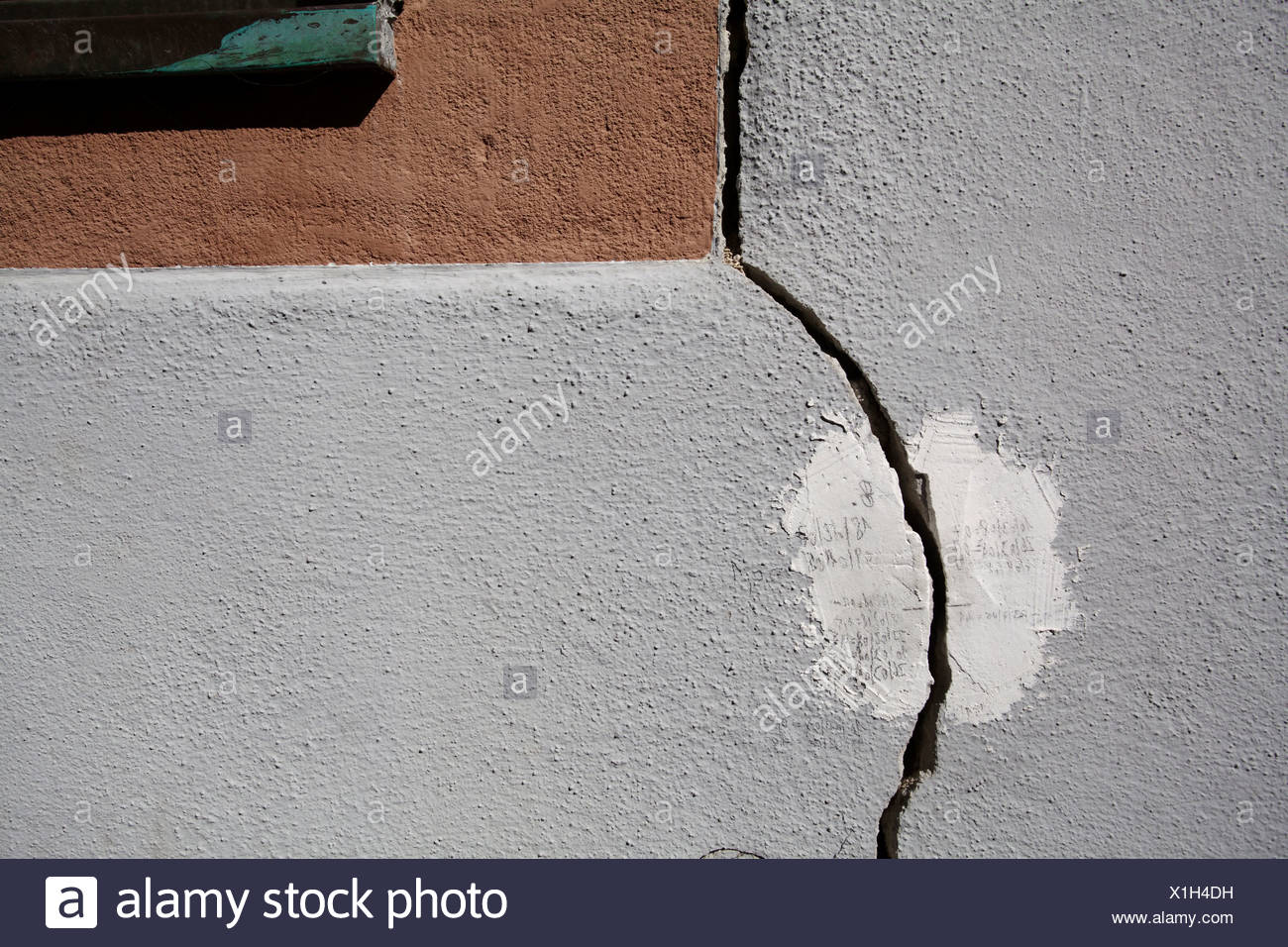 Cracks on the facade of a house caused by the elevating ground, a result of geothermal drilling in the area, historic district - Stock Image