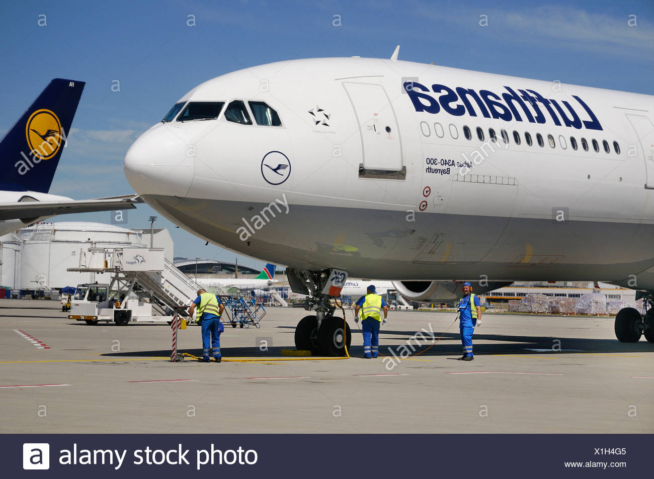 Maintenance personnel next to a Lufthansa plane - Stock Image