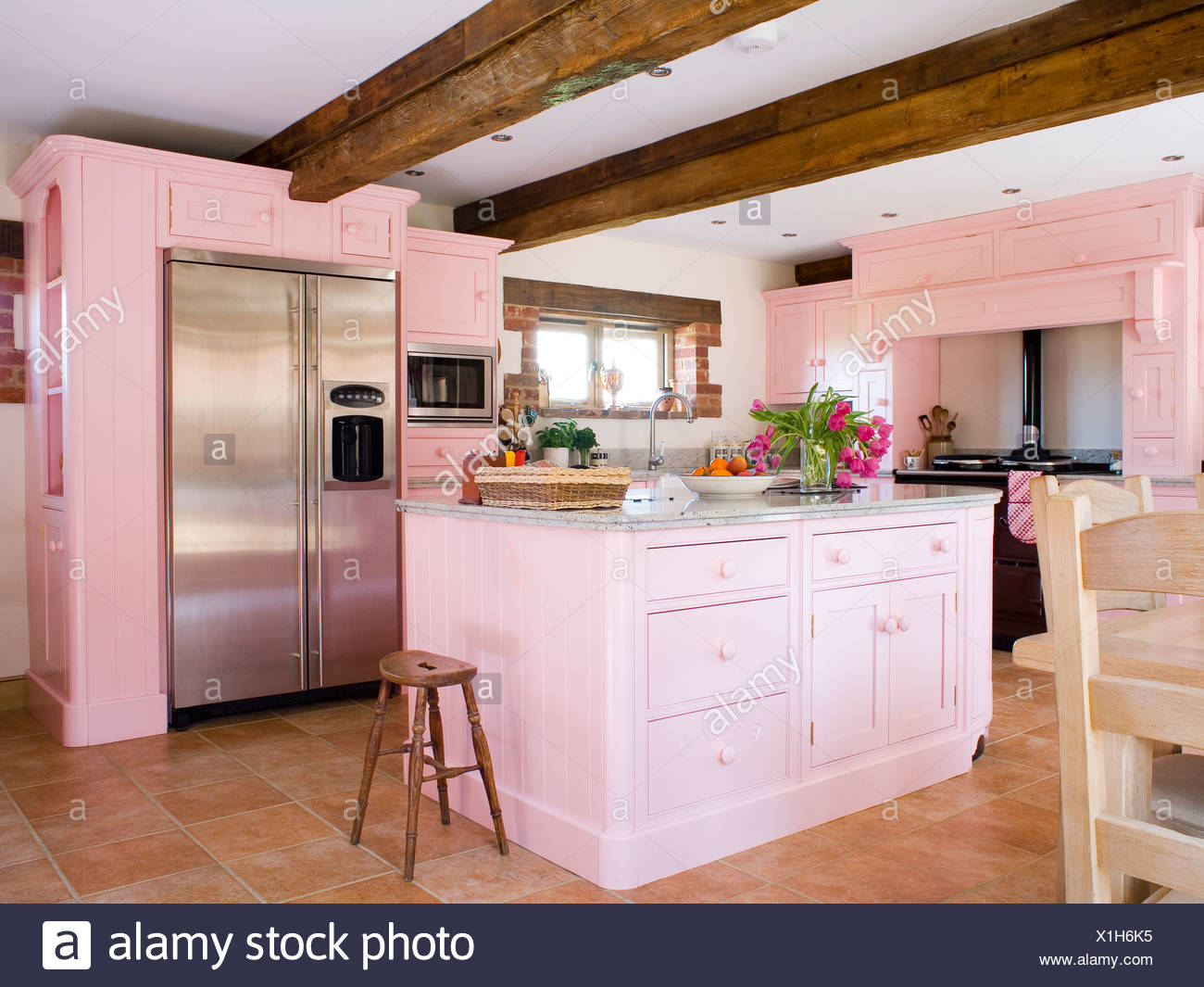 Pastel Pink Fitted Units And Island Unit In Country Kitchen With