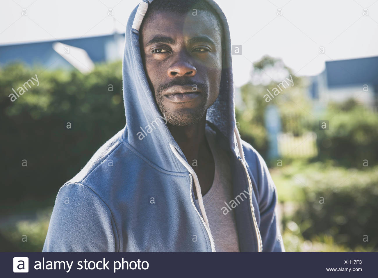 Portrait of man wearing hooded top looking away - Stock Image