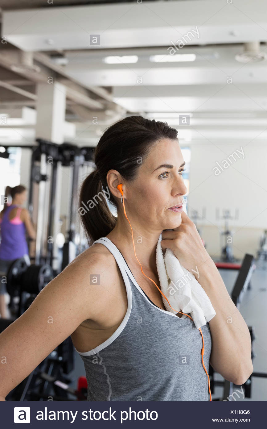 Woman with towel resting at gym - Stock Image