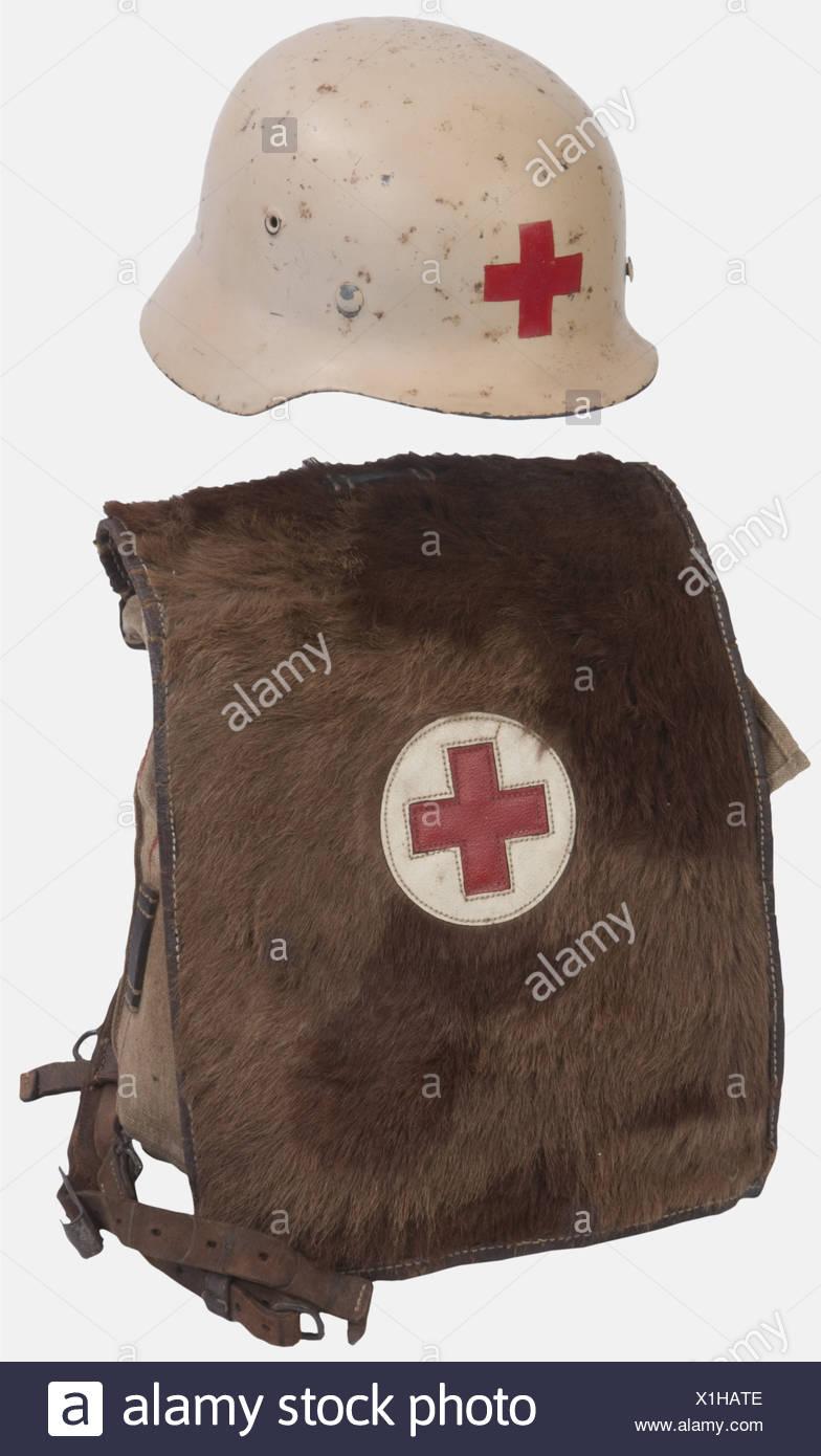 WEHRMACHT, Ensemble infirmier Heer, comprenant un casque modèle 40 feldgrau repeint (postérieurement) en blanc avec croix rouge complet de son intérieur et jugulaire et un sac peau de vache d'infirmier avec croix rouge sur le rabat, complet avec ses bretelles, , Additional-Rights-Clearances-NA - Stock Image