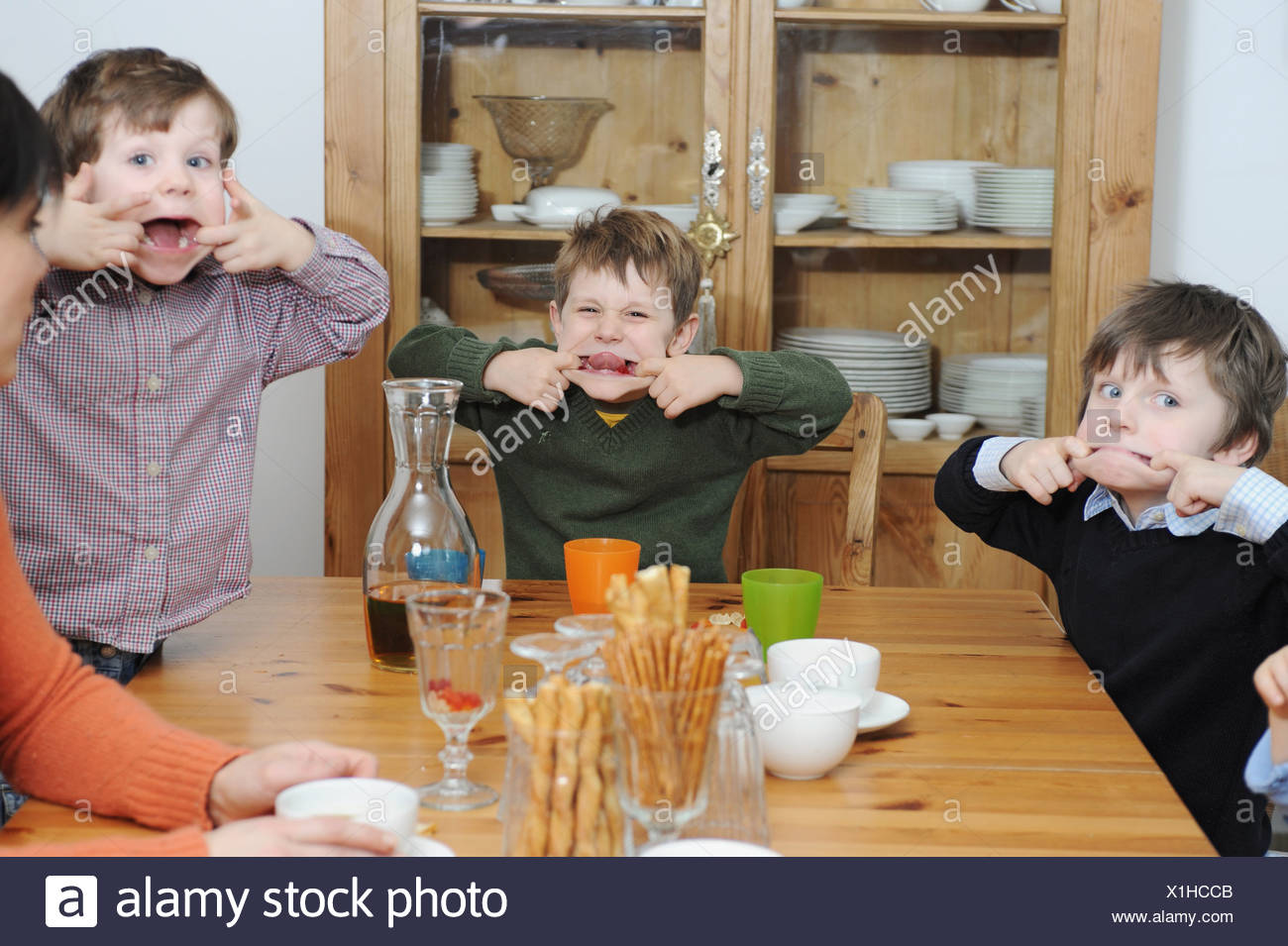 Boys making faces at table - Stock Image
