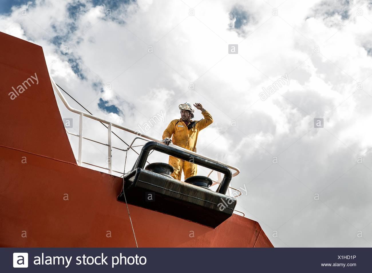 Worker mooring oil tanker on deck making hand gesture - Stock Image