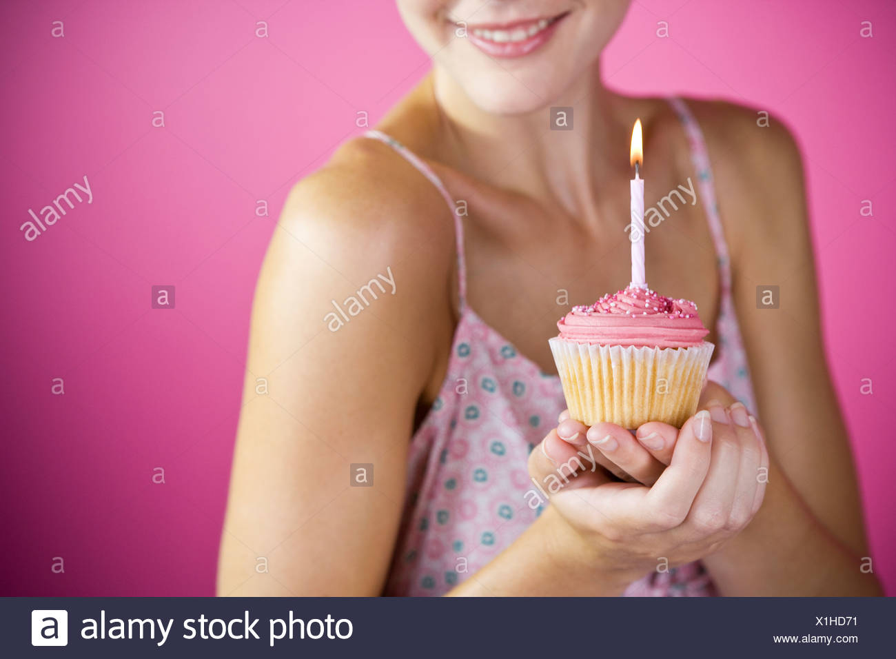 A Young Woman Holding A Birthday Cake With A Candle - Stock Image