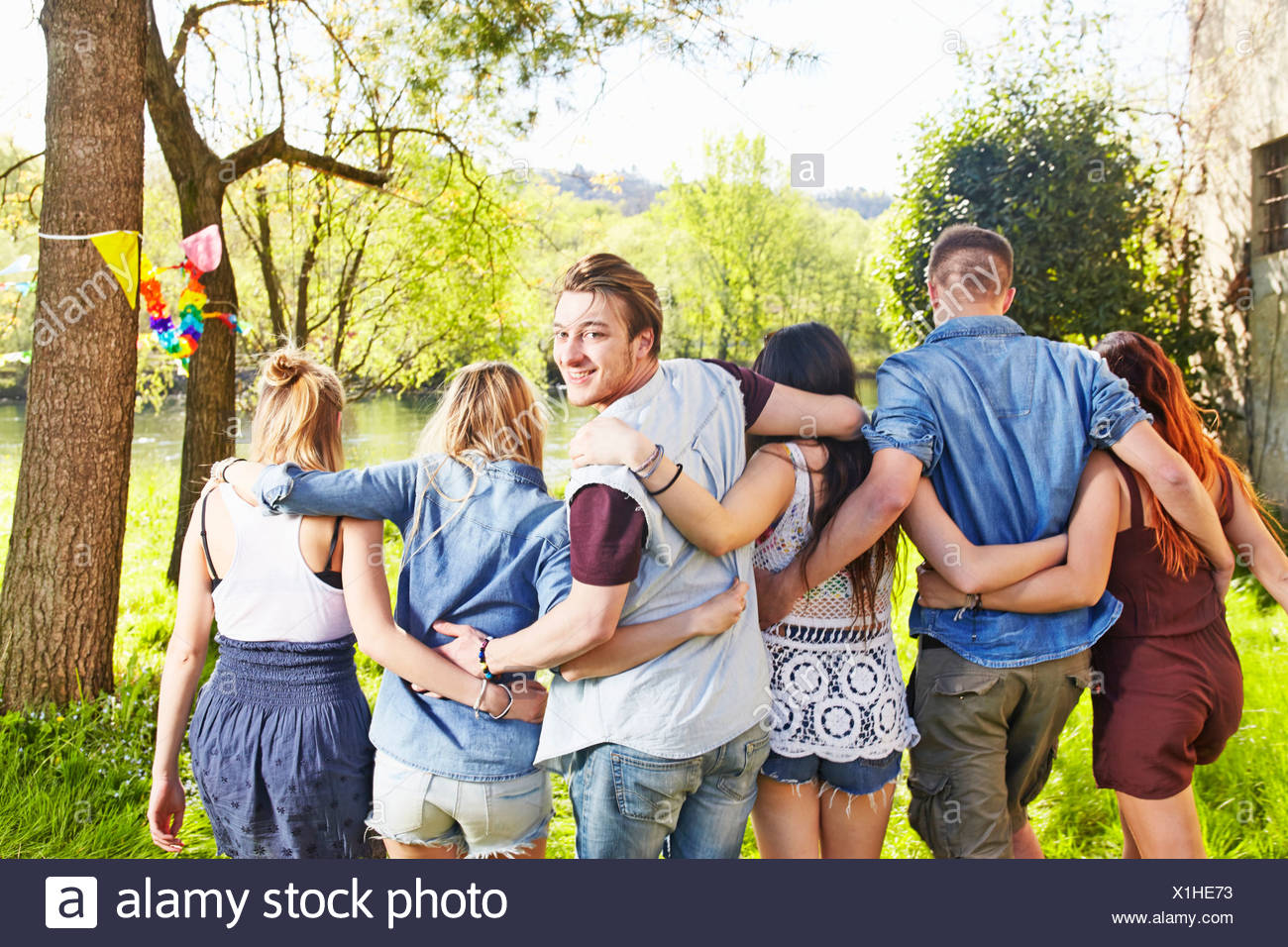 Group of friends with arms around each other - Stock Image