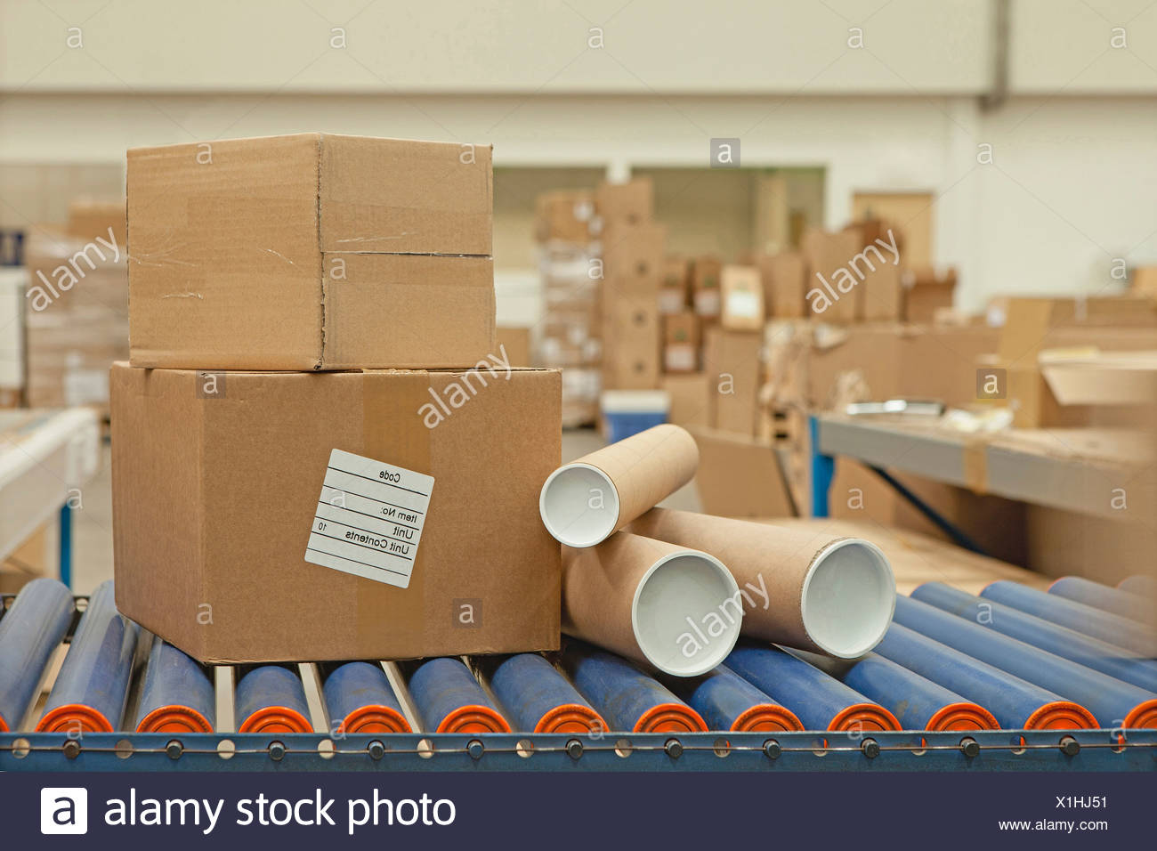 Cardboard boxes and tubes on conveyor belt - Stock Image