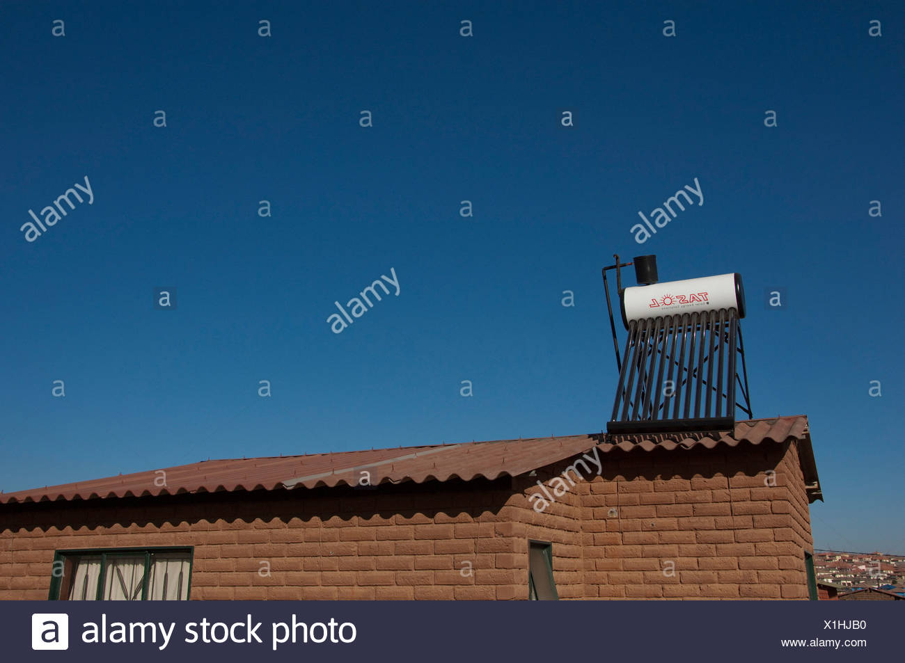 Landscape shot of a rural home with solar powered heating on the roof - Stock Image