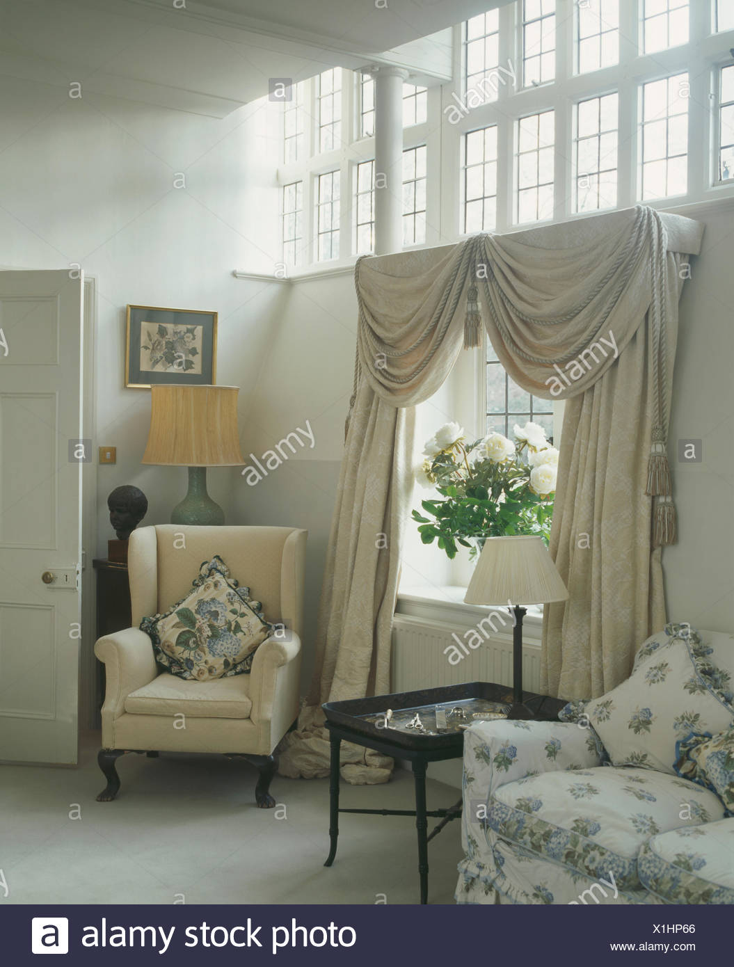 Cream swagged and tailed curtains at window in country ...