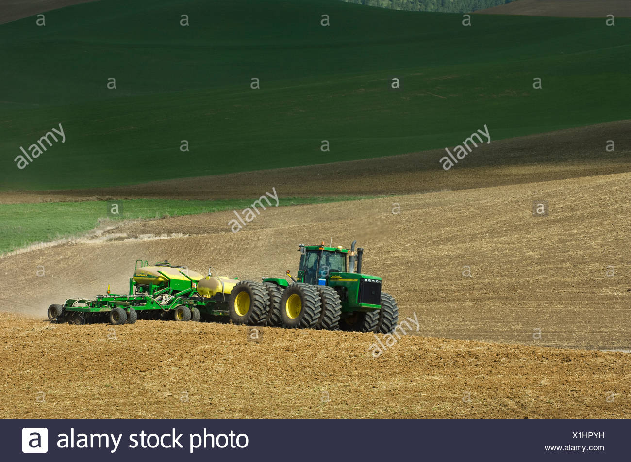 A John Deere tractor and air seeder planting garbanzo beans (chick peas) in the rolling hills of the Palouse / Washington, USA. - Stock Image