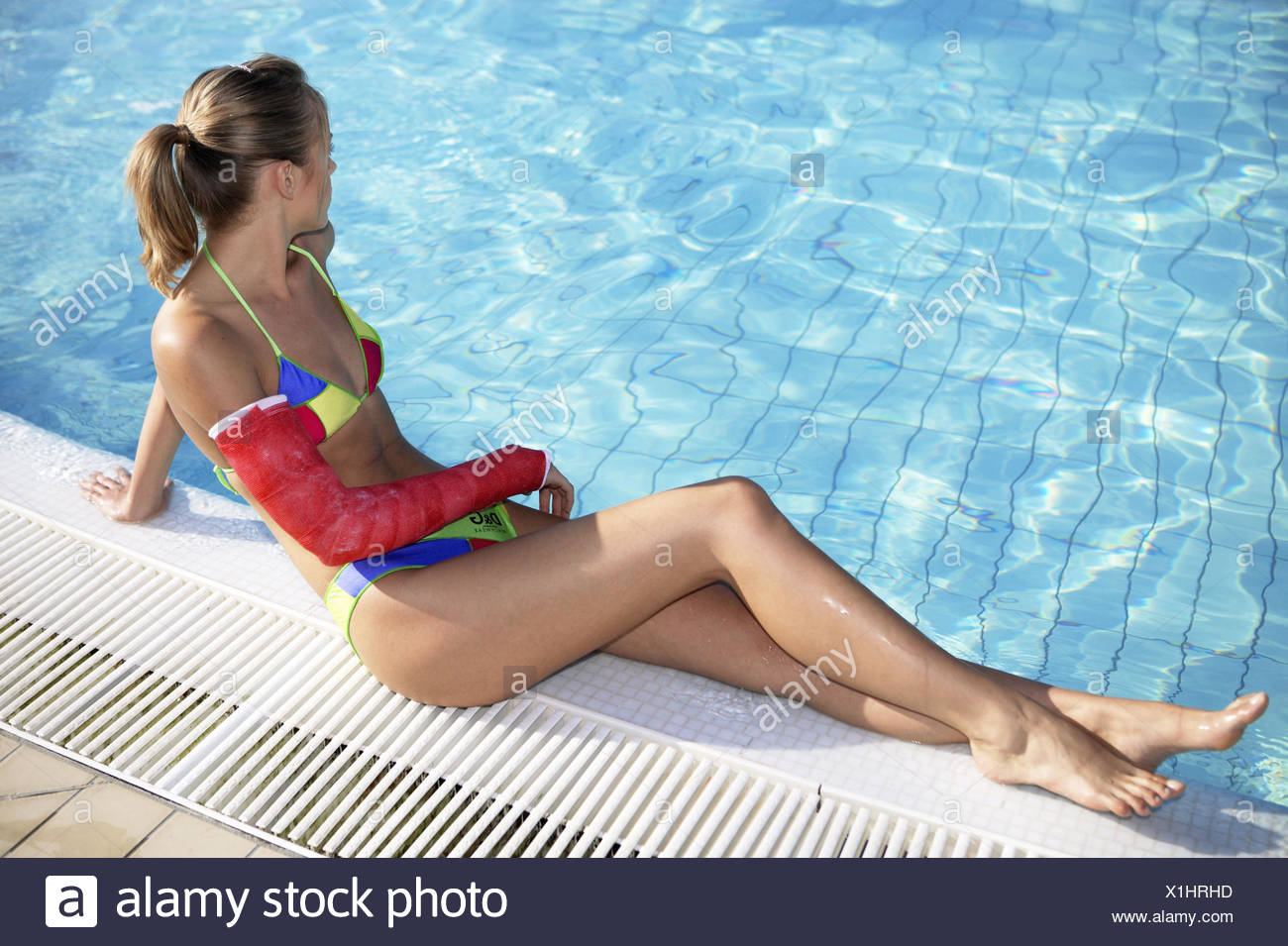 Frau Jung Arm Gips Schiene Gebrochen Pool Sitzen Sommer Urlaub Holiday Unfall Verletzung Armbruch Behinderung Schicksal Traurig - Stock Image