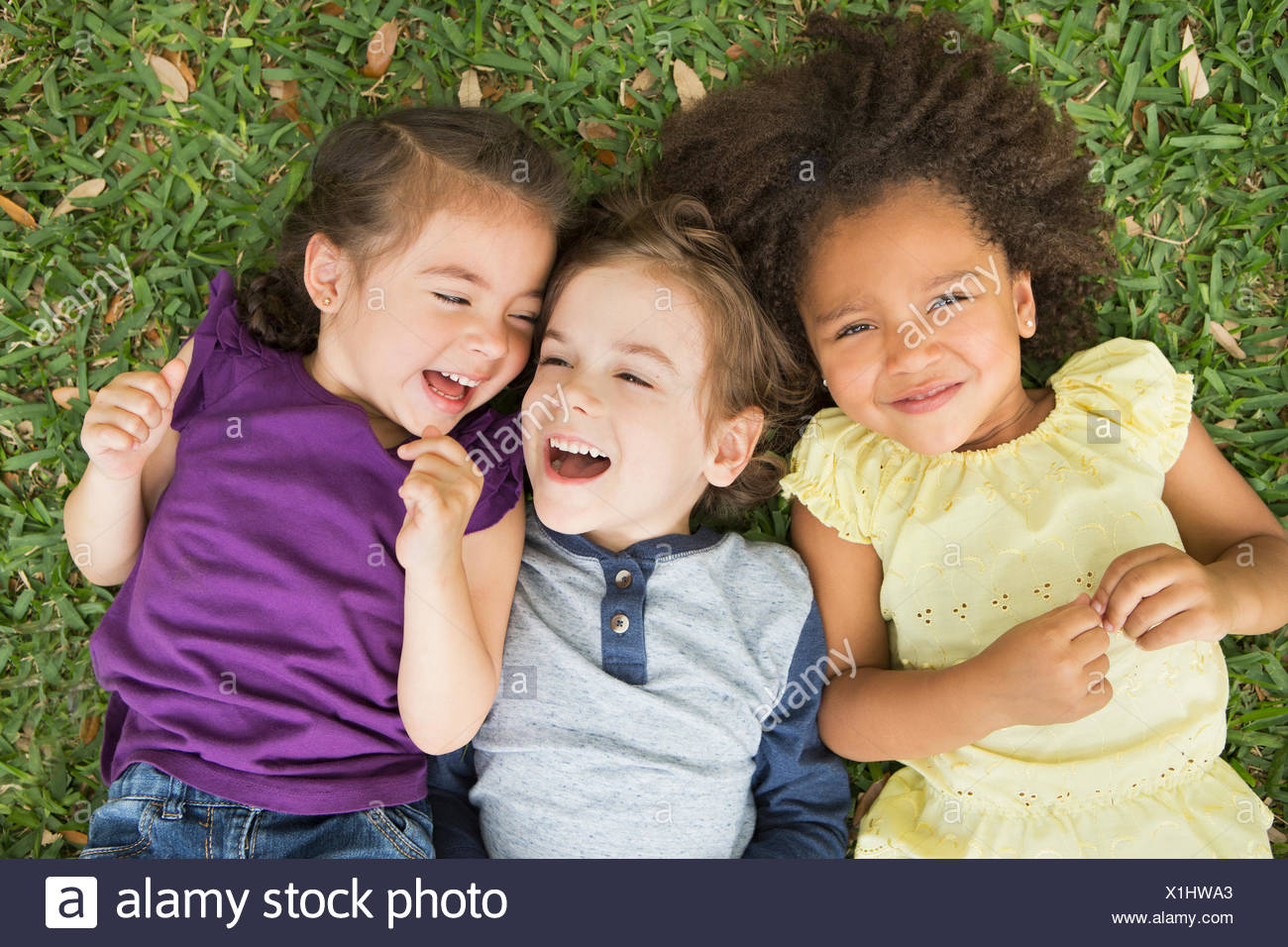 Three children lying on their backs on the grass, looking up and laughing. - Stock Image