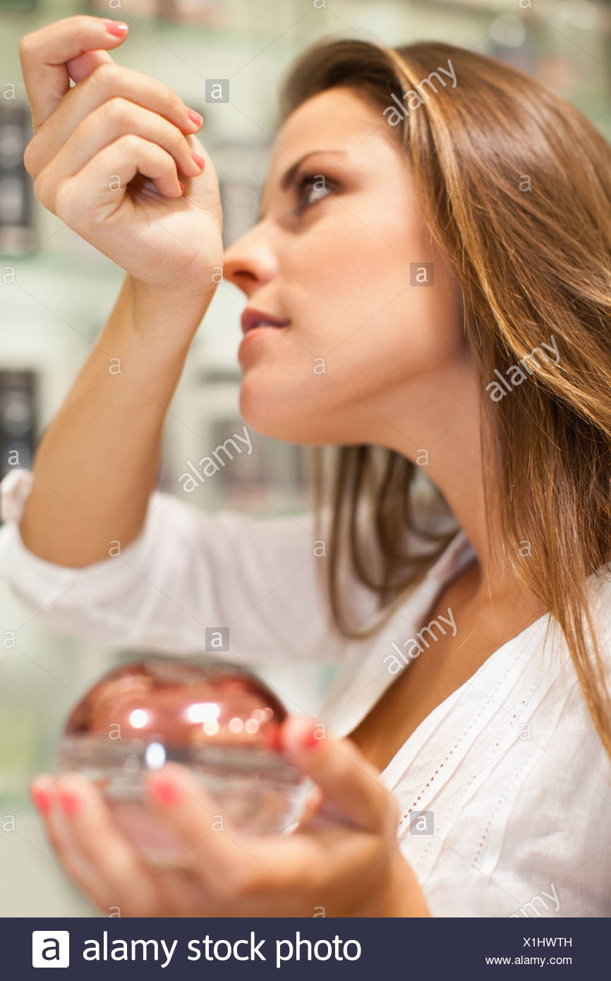 Woman trying on fragrances in store - Stock Image