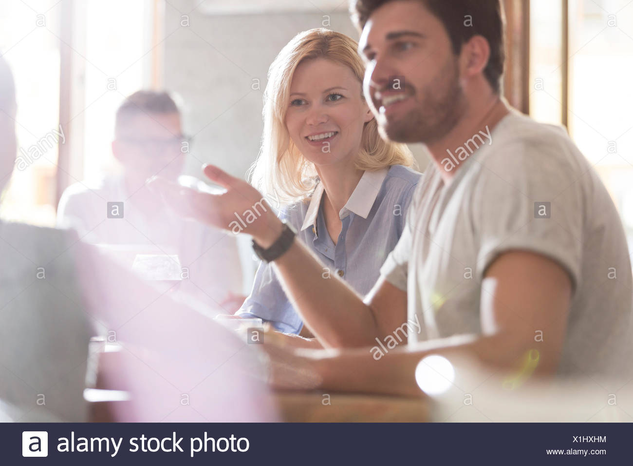 Smiling parents talking and gesturing to daughter at cafe - Stock Image