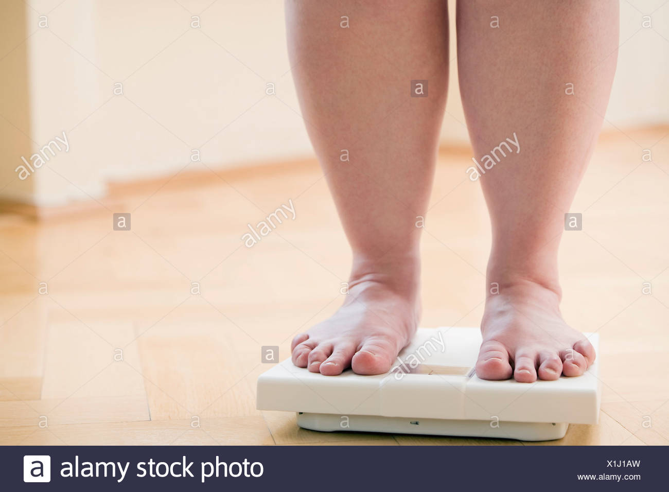 legs of overweight woman checking her weight on bathroom scales - Stock Image