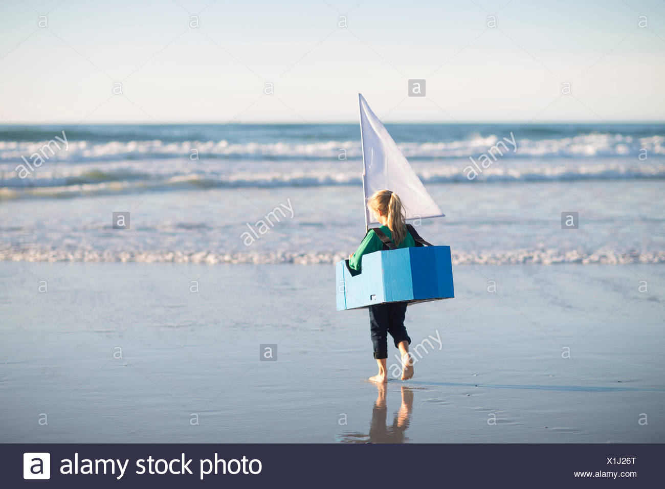 Girl running with toy boat into sea - Stock Image