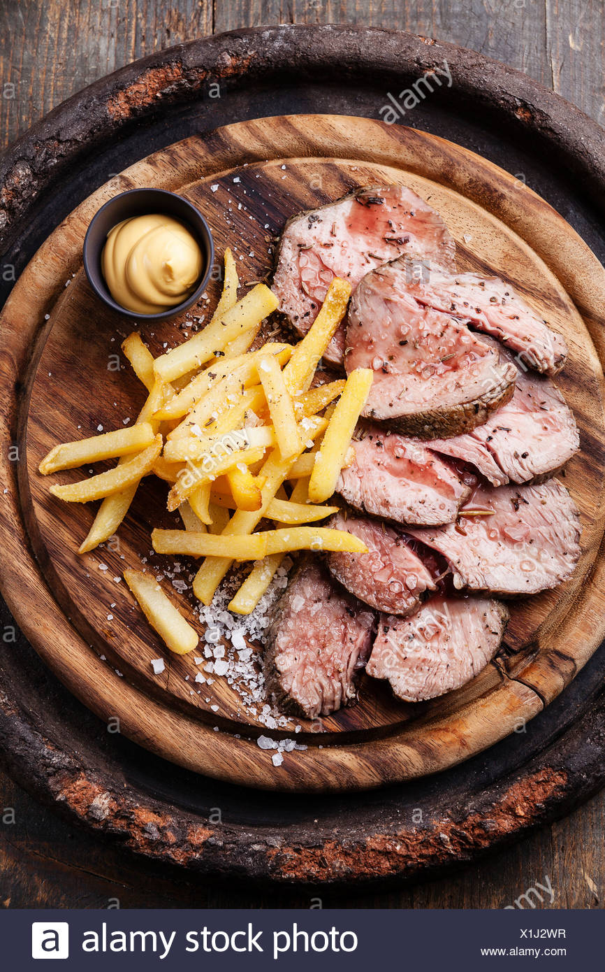 Roast beef with Salted french fries on cutting board - Stock Image