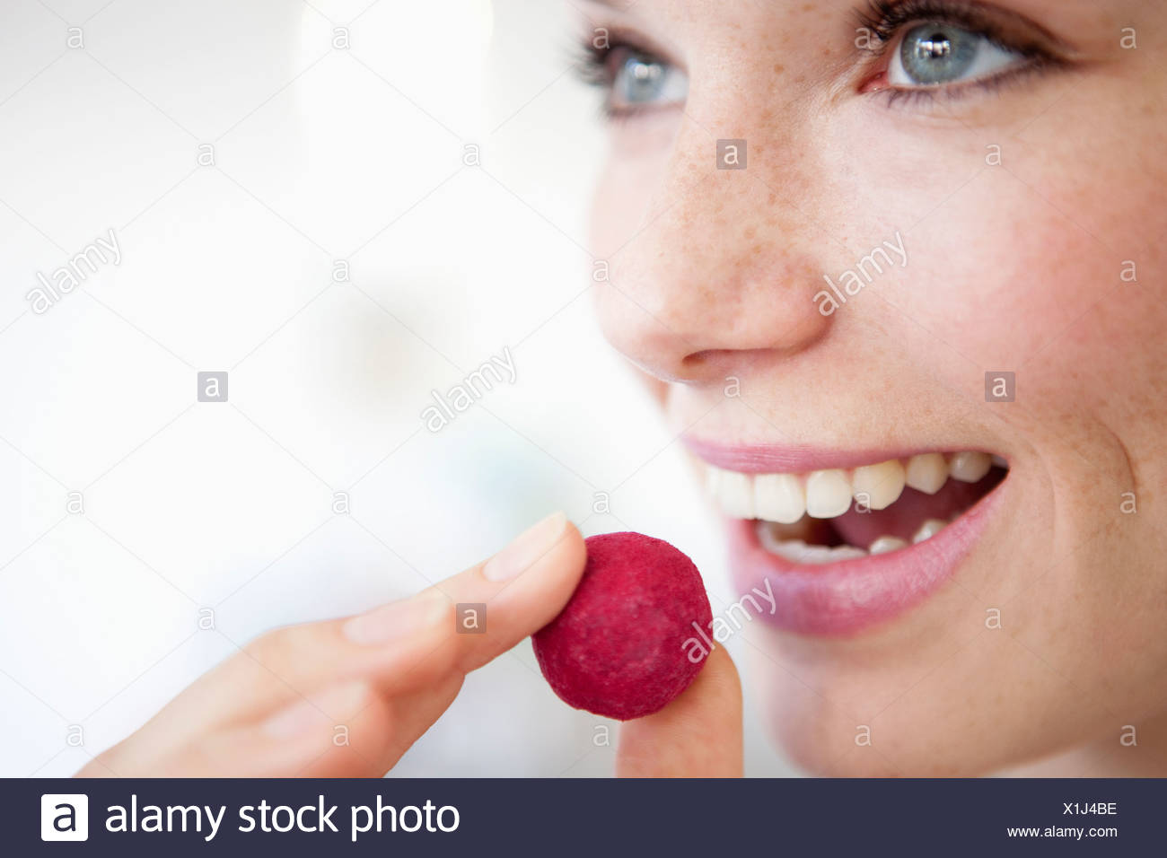 A woman eating a fruit flavored chocolate truffle - Stock Image