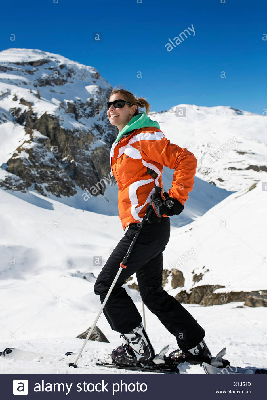 Famale sking doing snowsports on a snow mountain in Val D'Isere with an orange jacket on a sunny day Stock Photo