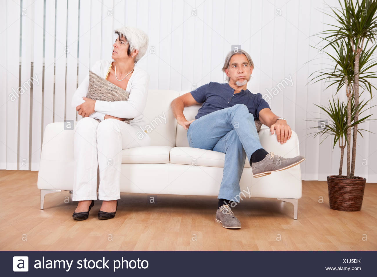 Senior couple after an argument sitting at opposite ends of the sofa sulking and looking away from each other into the distance - Stock Image