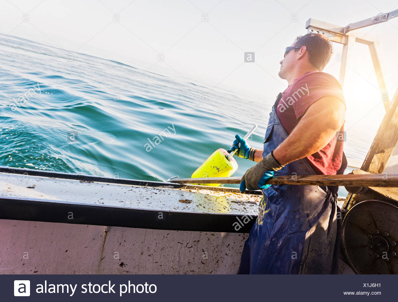 Fisherman throwing lobster buoy - Stock Image