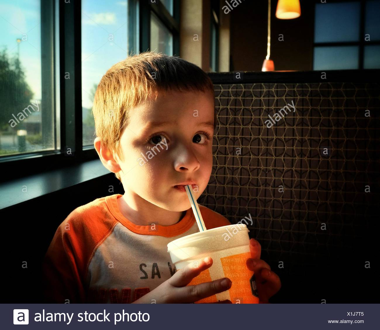 Close-Up Portrait Of Cute Boy Drinking While Sitting In Restaurant Stock Photo