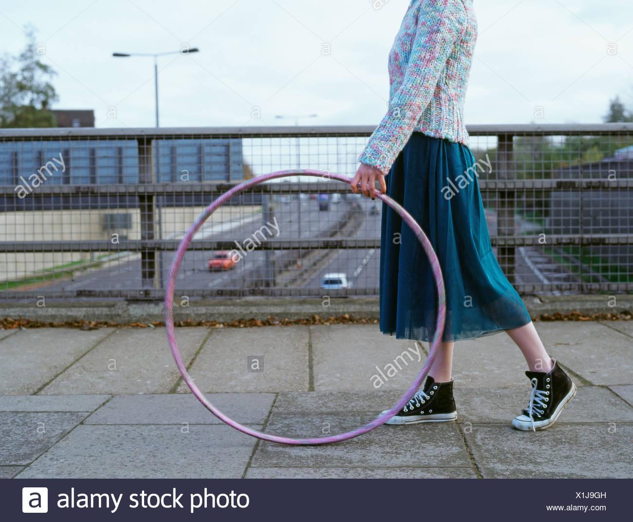 Woman with hula hoop on motorway bridge - Stock Image