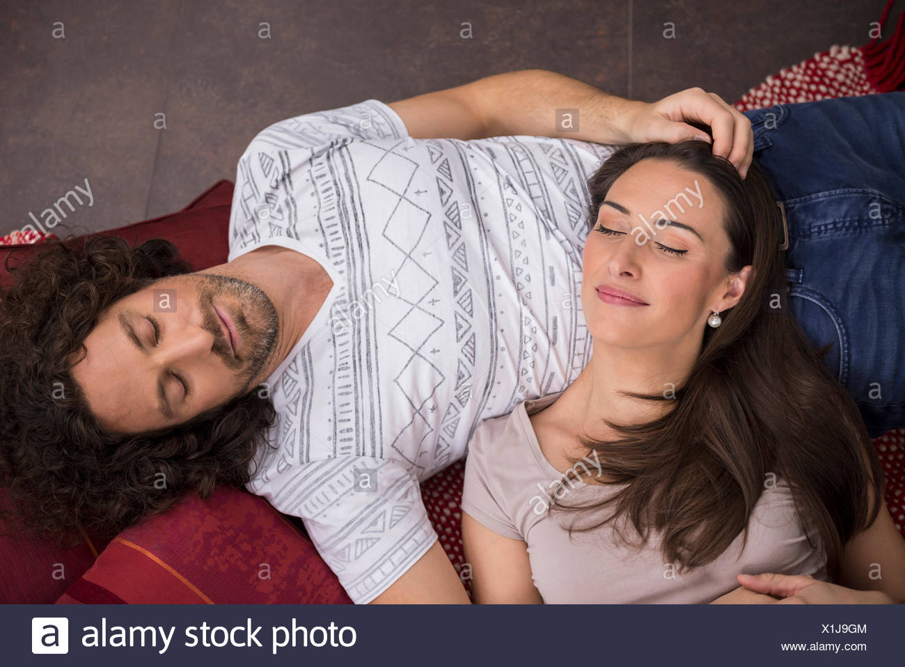 High angle view of mid adult couple sleeping on floor, Munich, Bavaria, Germany - Stock Image