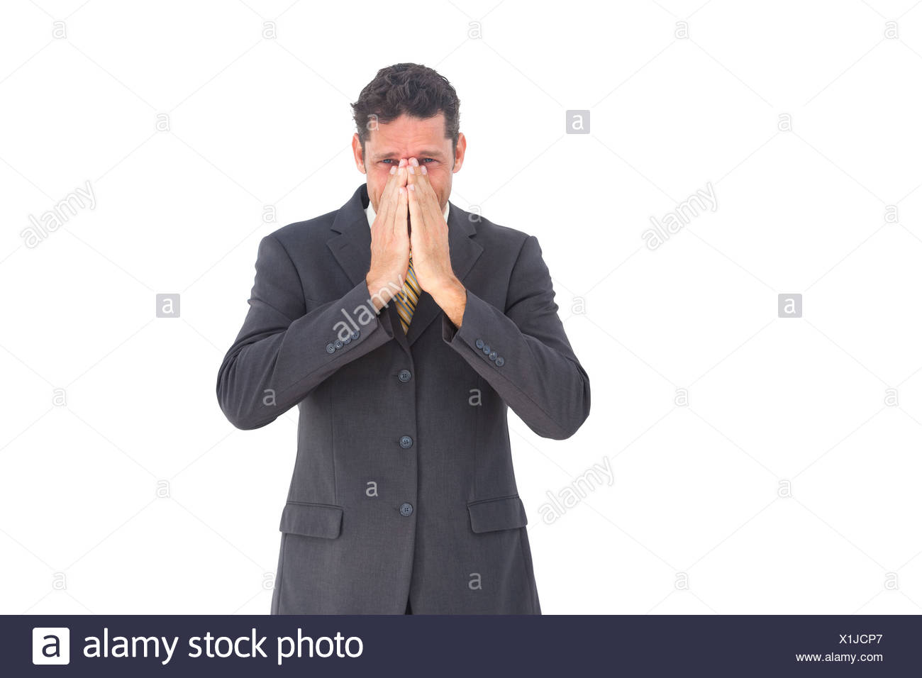 Apprehensive businessman looking at the camera - Stock Image