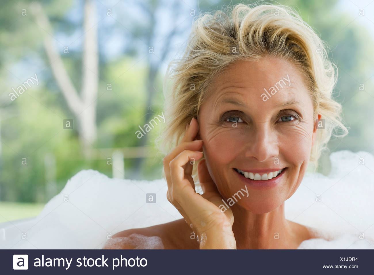 Mature woman relaxing in bubble bath, portrait - Stock Image