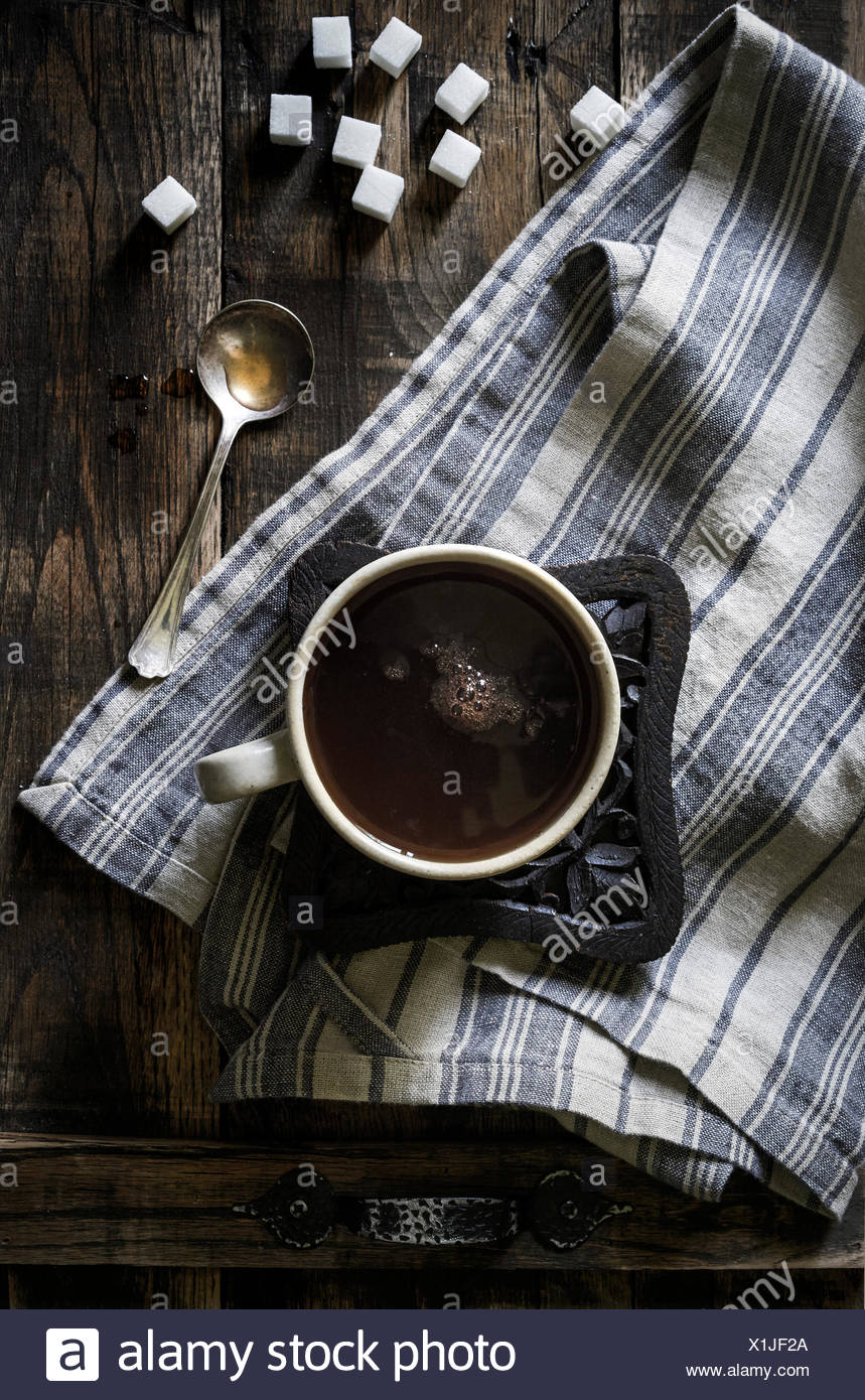 Hot mug of tea on rustic wood trivet and linen on a dark wood tray with sugar cubes and vintage spoon. - Stock Image