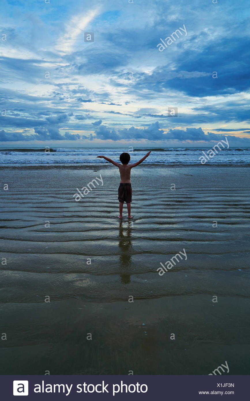 Rear view of boy standing with his arms in the air on the beach - Stock Image