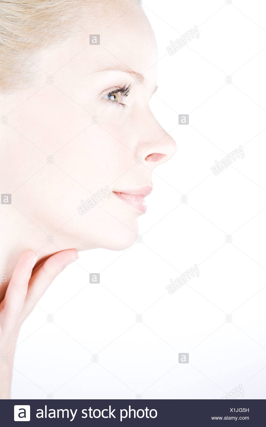 Profile of a young woman with her hand on her neck - Stock Image