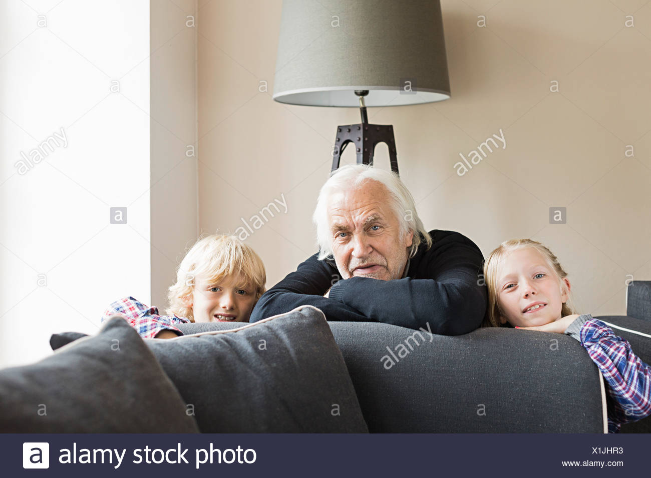 Portrait of grandfather and grandchildren leaning on sofa - Stock Image