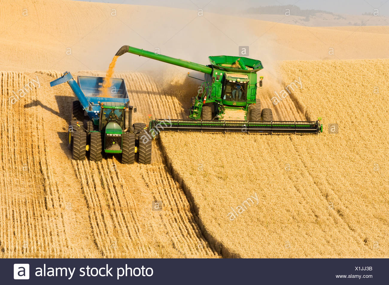 "A John Deere combine harvests Soft White wheat on rolling hillside terrain and unloads into a grain wagon ""on-the-go"" / USA. - Stock Image"