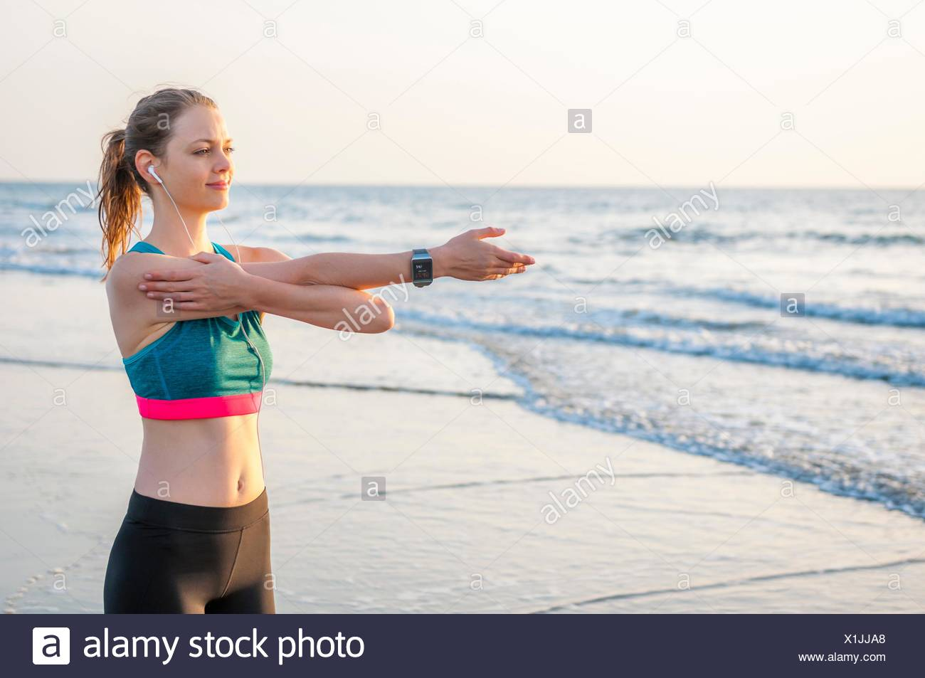 Mid adult woman by ocean wearing earbuds and crop top arm out stretching, looking away - Stock Image