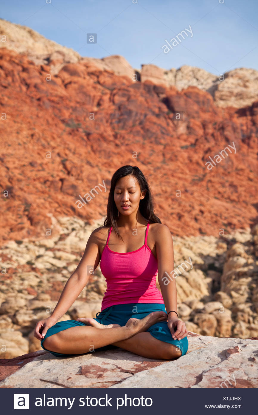 A fit young asian woman practicing yoga while on a rock climbing trip, Red Rocks, Las Vegas, Nevada, United States of America - Stock Image