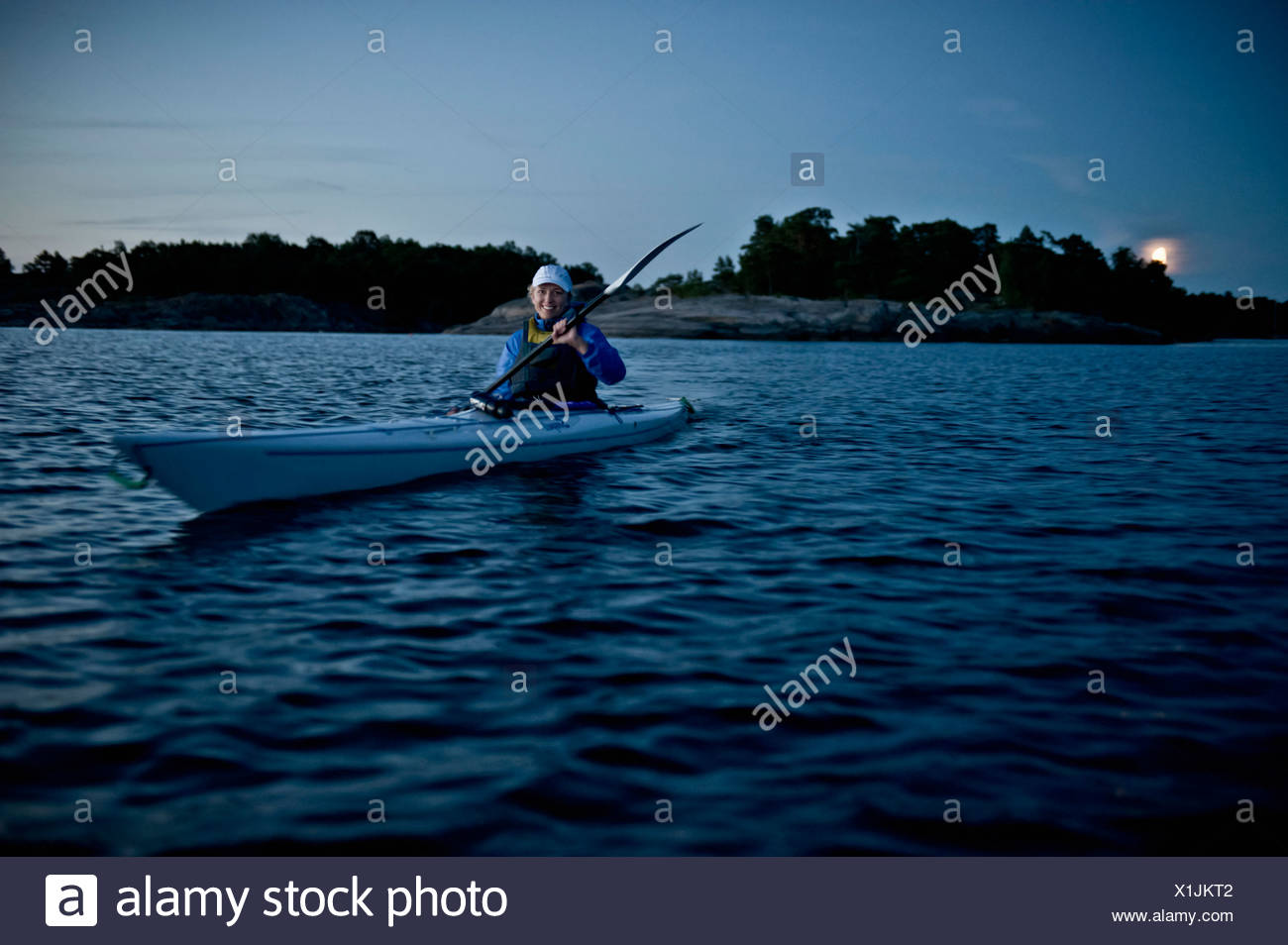 Smiling woman in nautical vessel oaring - Stock Image