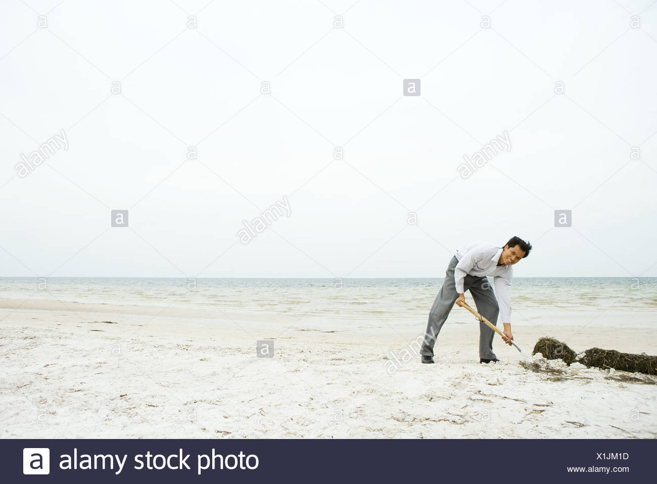 Man at the beach, bending over and digging in sand, smiling at camera - Stock Image
