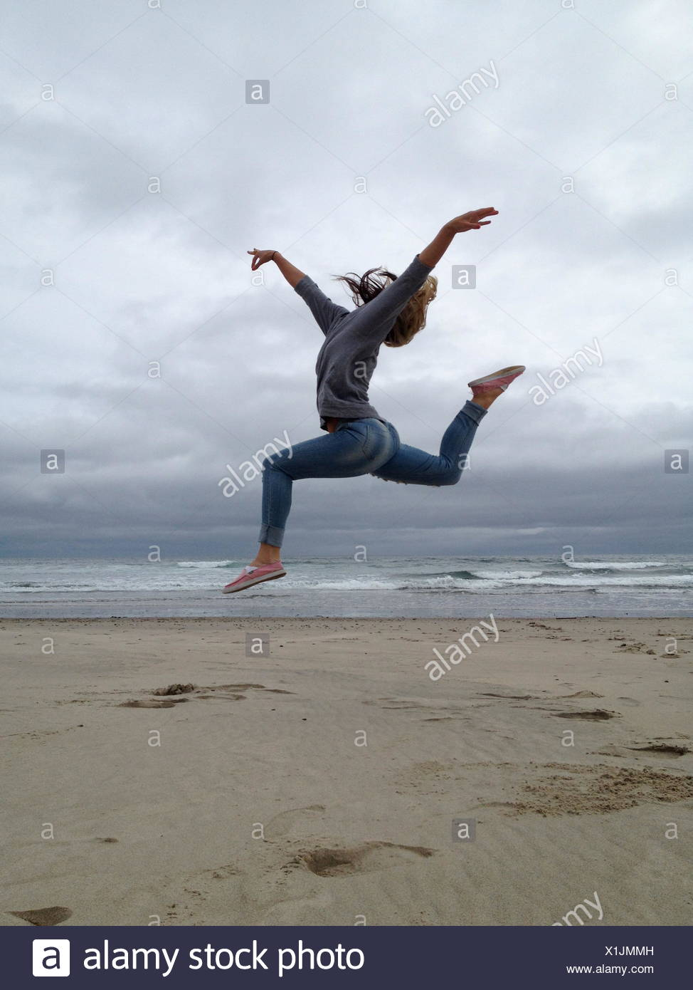 USA, Oregon, Tillamook County, Rockaway Beach, Young woman practicing ballet on beach - Stock Image