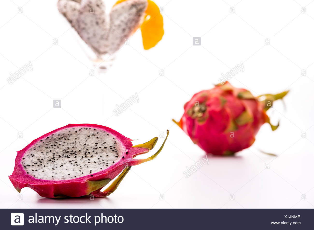 The blazing white and mildly aromatic pulp of the pitaya is suited for a quenching desert. Best served chilled. Assorted in a glass or in its halved rind. - Stock Image