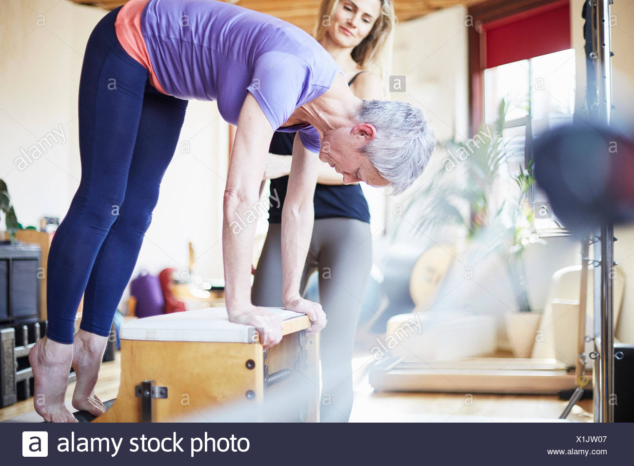 Mature female student bending over combo chair in pilates gym - Stock Image