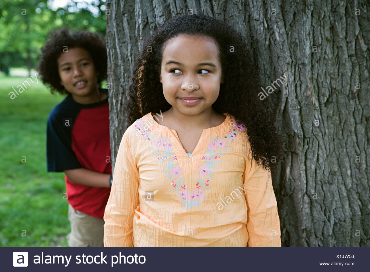 Girl and boy playing hide and seek - Stock Image