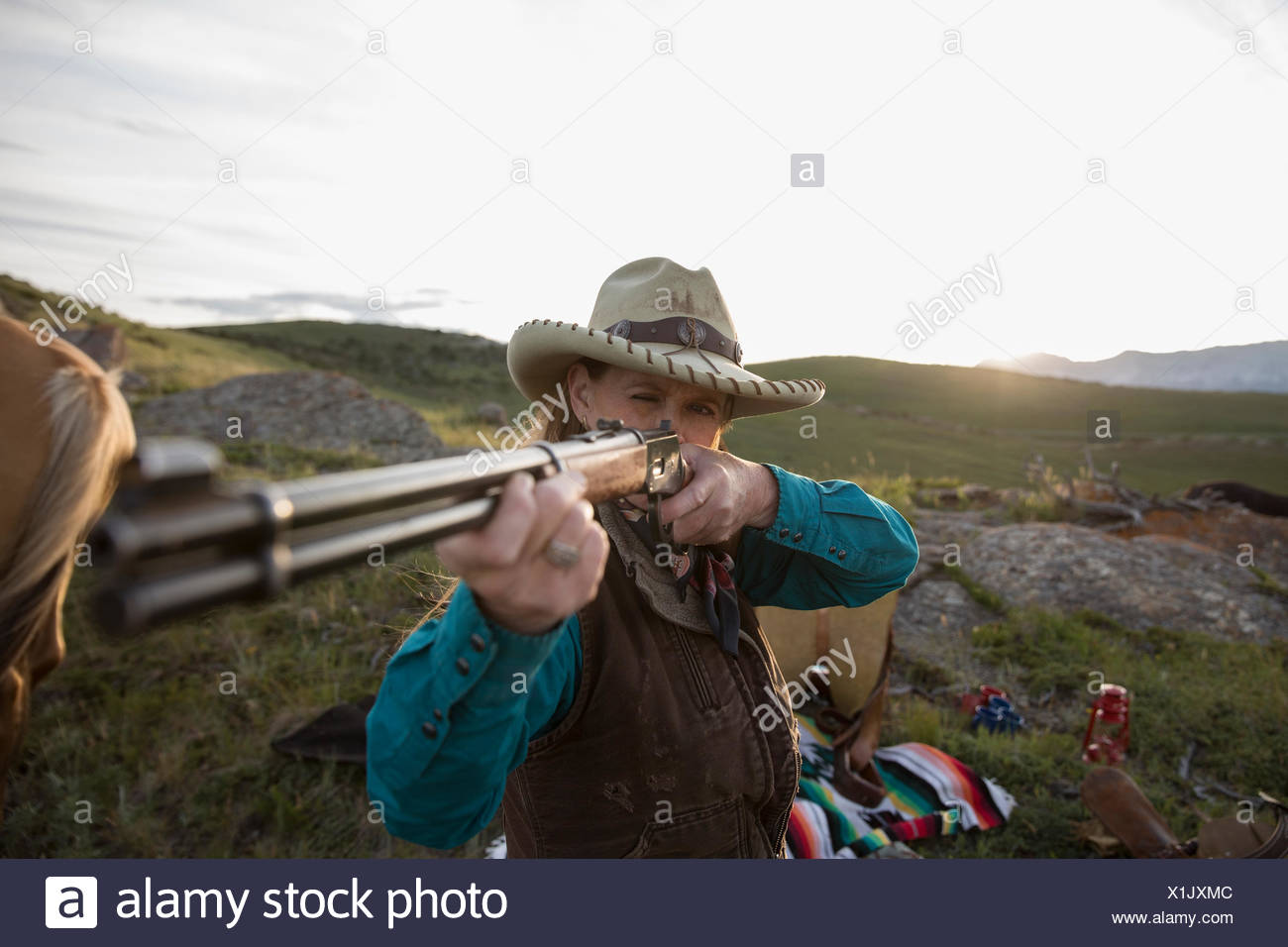 Female rancher aiming rifle in remote field - Stock Image
