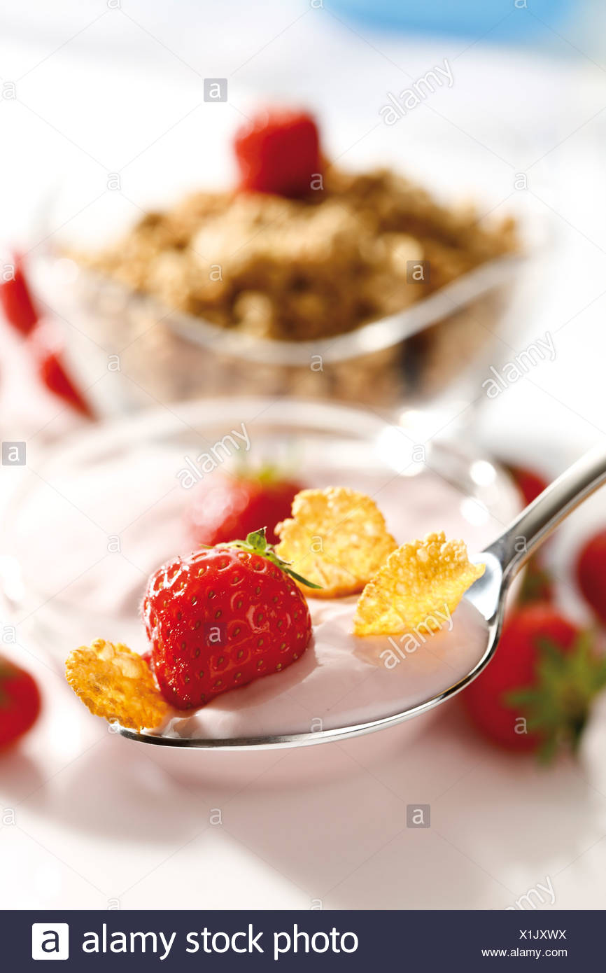 Strawberry yoghurt with cornflakes on a spoon, muesli Stock Photo