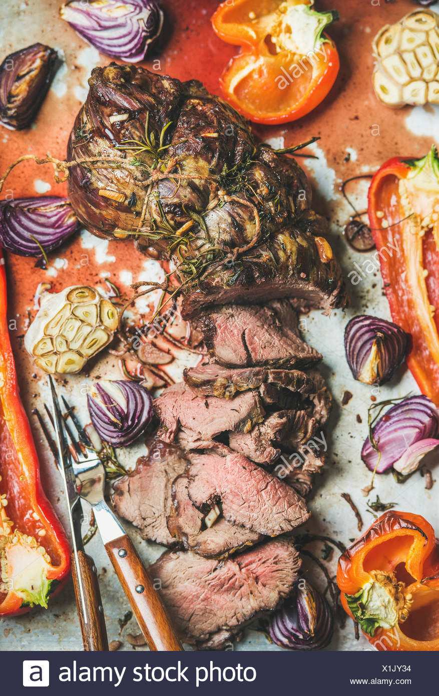 Cooked Roast beef meat with roasted vegetables and herbs in metal baking tray, top view, vertical composition. Slow food concept - Stock Image